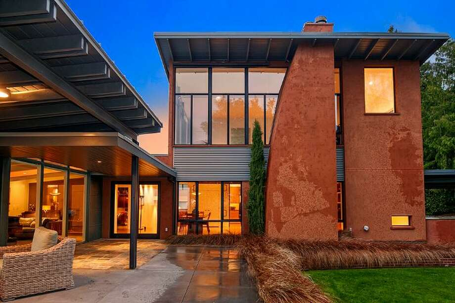 Exterior of 5530 60th Ave N.E. The 5,150-square-foot house, built in 1955, but extensively updated, has four bedrooms, 4.25 bathrooms, a great room, an office, three fireplaces, walls of windows, built-ins and a covered patio on more than one-third of an acre. It's listed for $2.2 million. Photo: Courtesy Mary Abbott, Windermere Real Estate