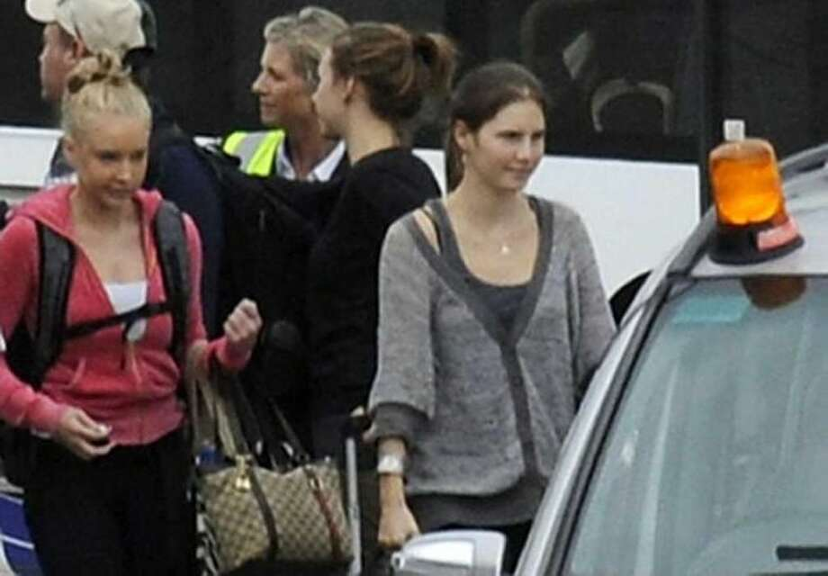 Amanda Knox, right, arrives from Rome with family members at Heathrow Airport London, Tuesday. Amanda Knox headed home to the United States a free woman Tuesday, after an Italian a assaulting and brutally slaying her British roommate. (AP Photo/Pool) Photo: ASSOCIATED PRESS, Anonymous / AP2011