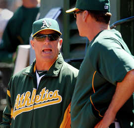 Chip Hale (left), who was named Arizona manager Monday, talks with A's manager Bob Melvin.