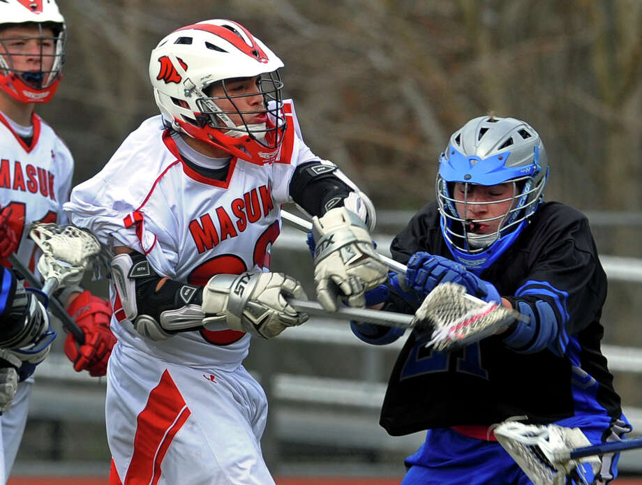 Masuk's Frank Bacarella follows through on a goal shot as Bunnell's Nolan Aurella, right, defends, during boys lacrosse action in Monroe, Conn. on Thursday April 18, 2013. Photo: Christian Abraham / Connecticut Post