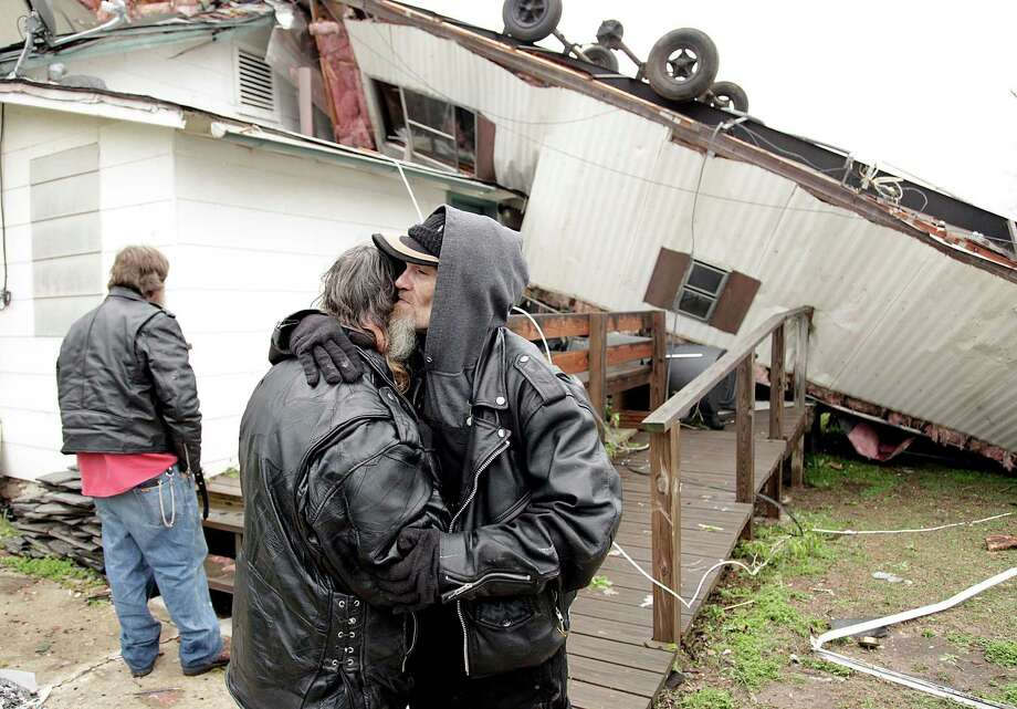 Candi Wear is comforted by her boyfriend, Mike Dollard, after a mobile home landed on top of their house when a storm hit Thursday in Spavinaw, Okla. Photo: MIKE SIMONS, MBI / Tulsa World