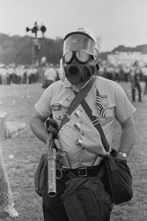 Portrait of a police officer in a gas mask as he stands with a riot gun in his hand and spare tear gas cartridges in his shirt during the 'Honor America Day Smoke-In' thrown by marijuana activists to protest the official 'Honor America Day' ceremonies being held at the Lincoln Memorial, Washington, DC, July 4, 1970. He has a mini American flag in one pocket and, perhaps ironically, a pack of cigarettes in the other. (Photo by David Fenton/Getty Images) Photo: David Fenton, Getty Images