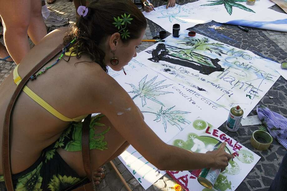 A youngster paints signs supporting the legalization of marijuana during a demonstration in Rio de Janeiro. (Photo by VANDERLEI ALMEIDA/AFP/Getty Images) Photo: VANDERLEI ALMEIDA, AFP/Getty Images