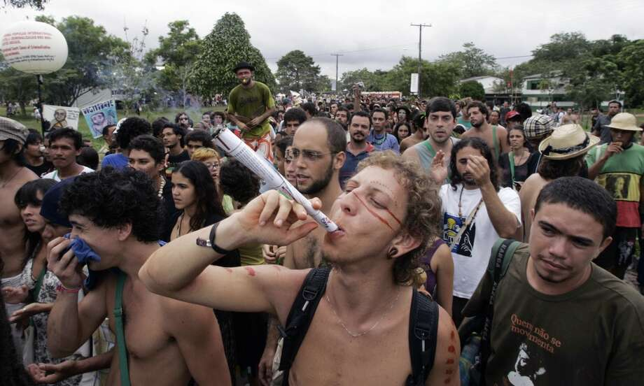 A young man smokes a giant marijuana cigar during a march in favor of its legalization during the World Social Forum in Belem, Para, northern Brazil on Jan. 31, 2009. (Photo by PAULO AMORIM/AFP/Getty Images) Photo: PAULO AMORIM, AFP/Getty Images