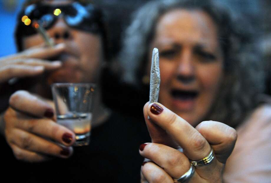 "A woman holds a marijuana joint during a protest in defense of the non-criminalization of the so-called ""personal dose"" in Medellin, Antioquia Department, Colombia on March 26, 2009. (Photo by RAUL ARBOLEDA/AFP/Getty Images) Photo: RAUL ARBOLEDA, AFP/Getty Images"