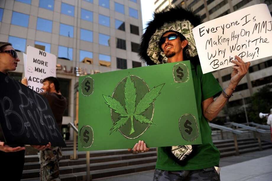 Rebecca Wright (left) and Christopher Stripling of Denver, join others to protest banks in the area closing their accounts with medical marijuana dispensaries on Aug 4, 2010. (Photo By Joe Amon/The Denver Post via Getty Images) Photo: Joe Amon, Denver Post Via Getty Images
