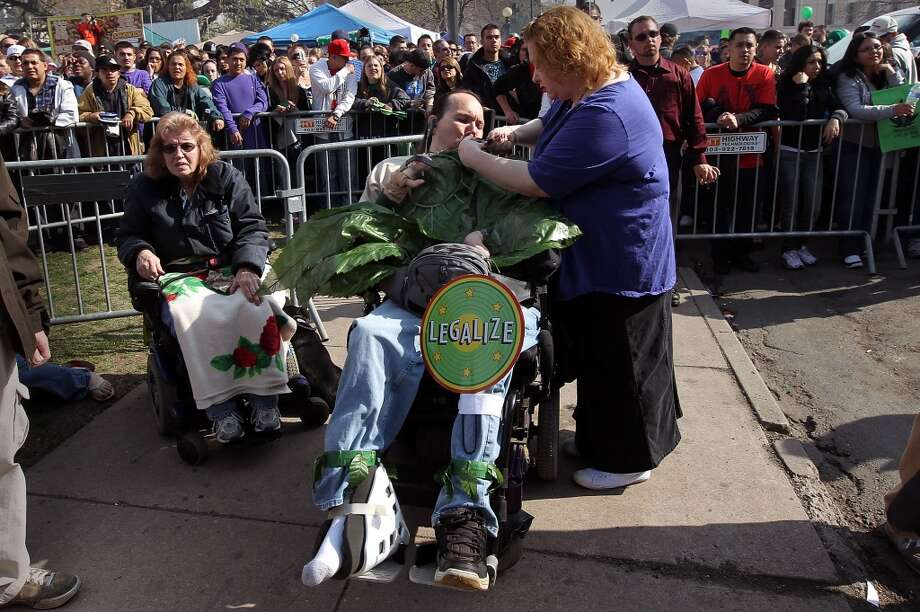 "Tracey Wood (R) lights a pipe filled with medical marijuana for her boyfriend Micah Moffet (C) at a pro-marijuana ""4/20"" celebration in front of the state capitol building April 20, 2010 in Denver, Colo. (Photo by John Moore/Getty Images) Photo: John Moore, Getty Images"