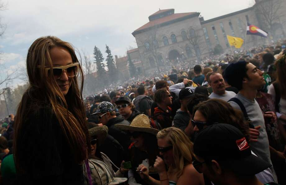 A young woman sits on the shoulders of a friend as a haze of marijuana settles on the crowd at 4:20 pm April 20, 2010 at the University of Colorado in Boulder, Colo. (Photo by Chris Hondros/Getty Images) Photo: Chris Hondros, Getty Images
