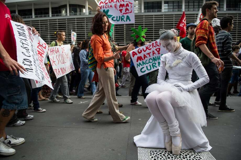 A woman performs in a living statue as a ballerina as protesters pass by during a demo for the legalization of marijuana in Sao Paulo, Brazil, on May 19, 2012.  (Photo by YASUYOSHI CHIBA/AFP/GettyImages) Photo: AFP, AFP/Getty Images