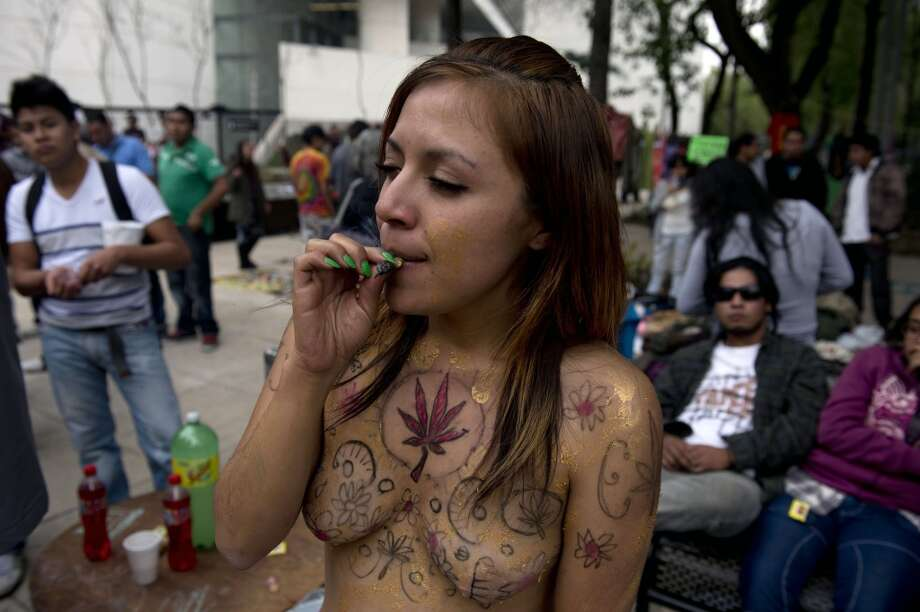 "A woman smokes marijuana as she poses with her body painted with marijuana leaves during the ""Marijuana Festival"" for its legalization at Luis Pasteur square, in front of building of the Mexican Senate on January 20, 2013 in Mexico City. (Photo by YURI CORTEZ/AFP/Getty Images) Photo: YURI CORTEZ, AFP/Getty Images"