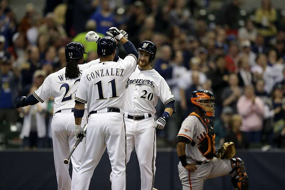Milwaukee Brewers' Jonathan Lucroy (20) is congratulated at home by teammates Alex Gonzalez and Rickie Weeks after Lucroy hit a two-run home run during the third inning of a baseball game against the San Francisco Giants Thursday, April 18, 2013, in Milwaukee. (AP Photo/Morry Gash) Photo: Morry Gash, Associated Press