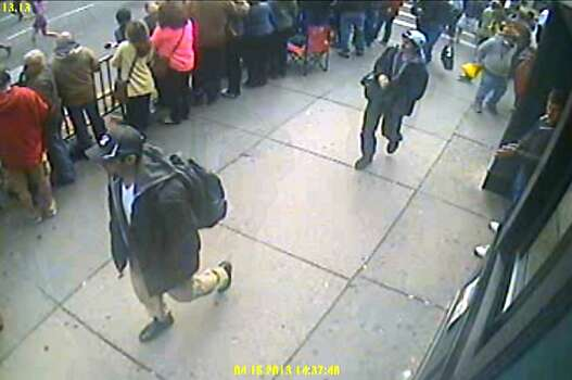 This frame grab from a video released by the FBI on Thursday, April 18, 2013, shows what the FBI are calling suspect number 1, front, in black cap, and suspect number 2, in white cap, back right, walking near each other through the crowd in Boston on Monday, April 15, 2013, before the explosions at the Boston Marathon. (AP Photo/FBI) Photo: Associated Press