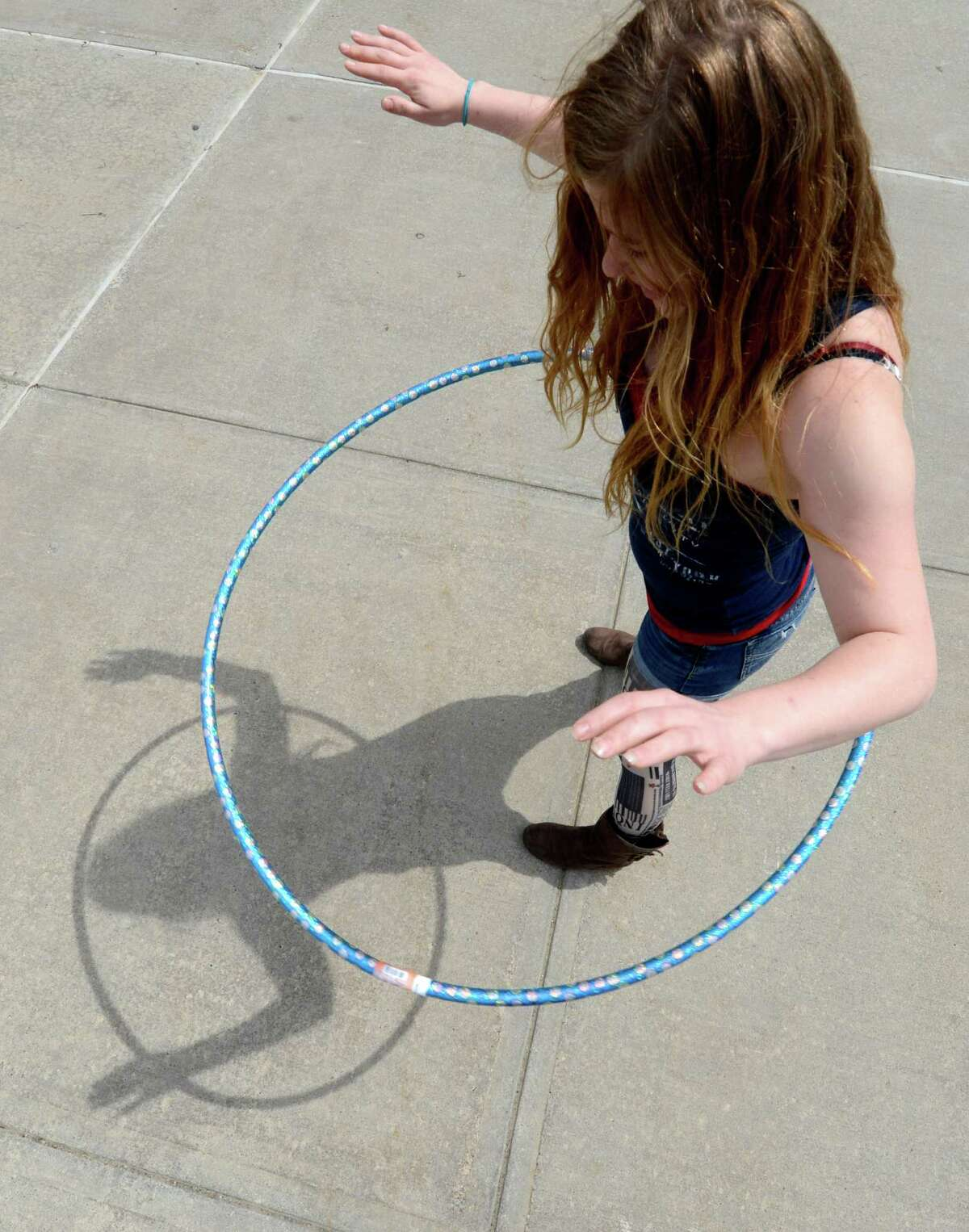 Elizabeth Kolvik 21 of Latham and a contestant in a hula hoop competition see her shadow during the warm up in the quad at Hudson Valley Community College Tuesday April 18, 2013 in Troy, N. Y. The competition was to twirl the hula hoop around your body and keep it moving around an obstacle course. There were very few takers in the contest. (Skip Dickstein/Times Union)