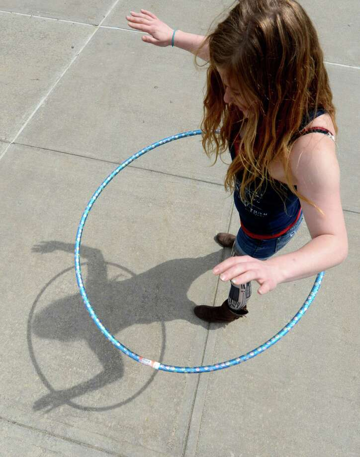 Elizabeth Kolvik 21 of Latham and a contestant in a hula hoop competition see her shadow during the warm up in the quad at Hudson Valley Community College Tuesday April 18, 2013 in Troy, N. Y.  The competition was to twirl the hula hoop around your body and keep it moving around an obstacle course.  There were very few takers in the contest. (Skip Dickstein/Times Union) Photo: SKIP DICKSTEIN / 0002022A