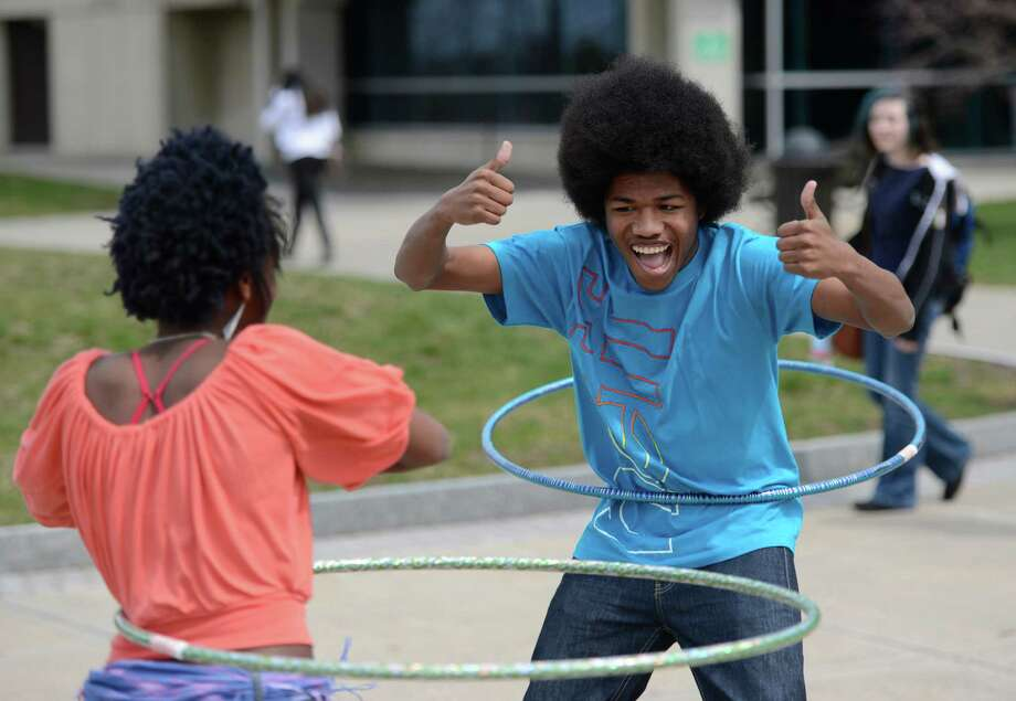 Naimah Peterkin, left and Shiquan Bishop, right, contestants in a hula hoop competition warm up with a little fun in the quad at Hudson Valley Community College Tuesday April 18, 2013 in Troy, N. Y.  The competition was to twirl the hula hoop around your body and keep it moving around an obstacle course.  There were very few takers in the contest. (Skip Dickstein/Times Union) Photo: SKIP DICKSTEIN / 0002022A