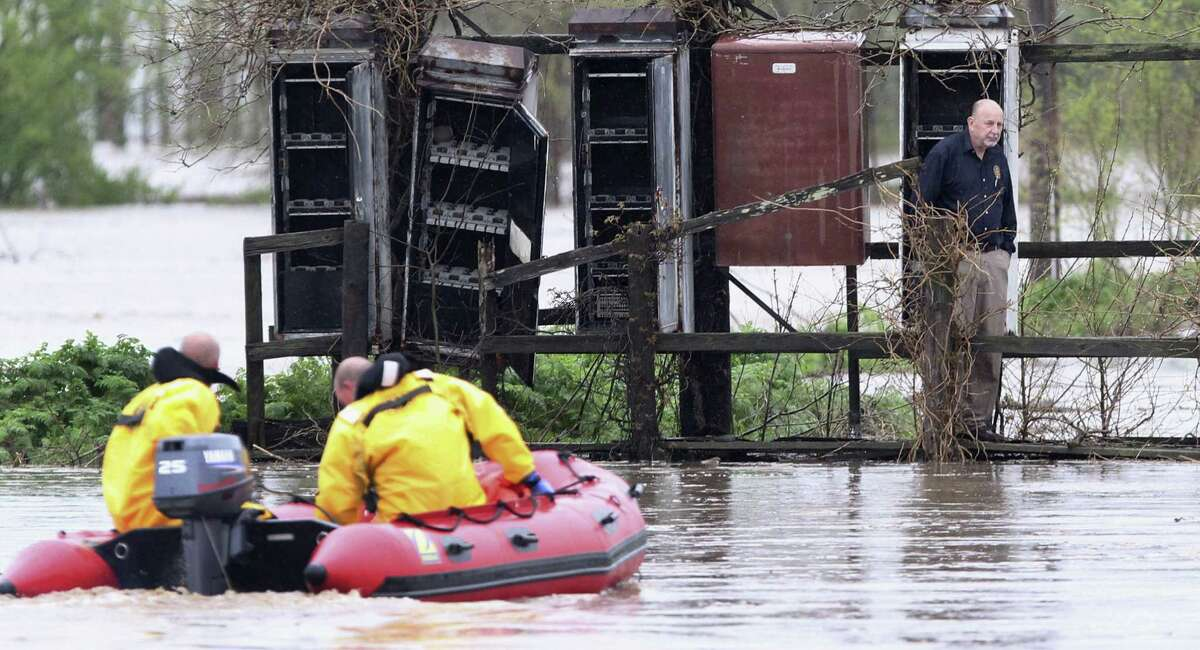 Smithton, Ill., firefighters Robert Lindauer and Cory Ellis use a boat to rescue Dan Bauer of Venedy, Ill., after Bauer's vehicle was engulfed in water on Route 158 in Mascoutah, Ill.