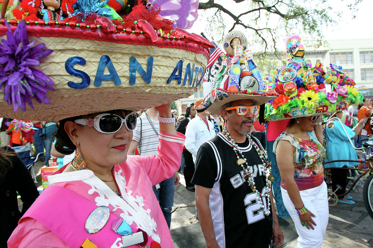 Pauline Grossman (from left) , Albert Limon and Dora Gonzalez get into the spirit with elaborate hats as Fiesta kicks off at the Alamo with King Antonio and Rey Feo on April 18, 2013.