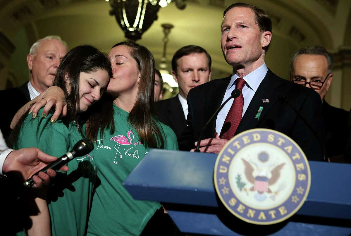 """U.S. Sen. Richard Blumenthal, D-Conn., talks about the """"despicable"""" filibuster. With him are (from left) Tucson, Ariz., shooting victim Bill Badger and Newtown, Conn., shooting victims' relatives Carlee Soto and Erica Lafferty."""