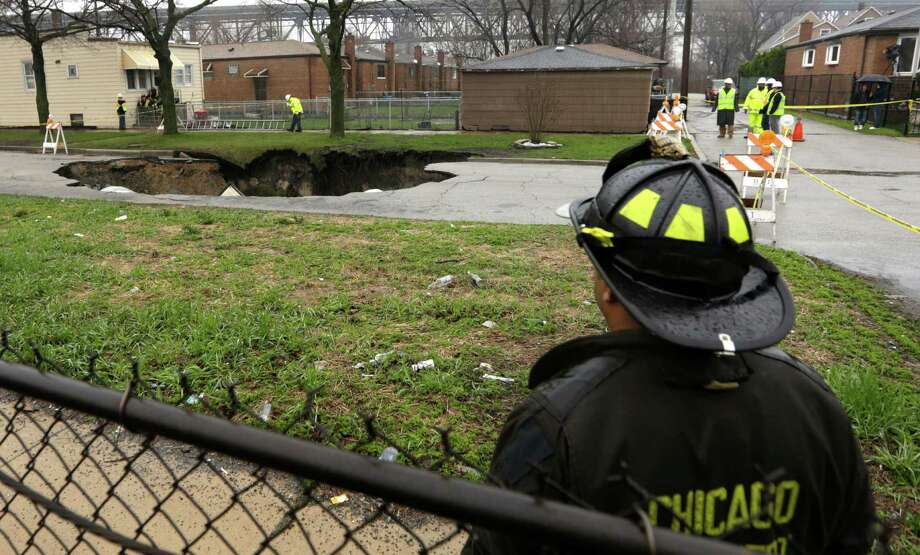 Officials survey a gaping sinkhole that opened up a residential street on Chicago's South Side after a cast iron water main dating back to 1915 broke during a massive rain storm, Thursday, April 18, 2013, in Chicago. The hole spanned the entire width of the road and chewed up grassy areas abutting the sidewalk. Two of the cars that disappeared inside had been parked, but a third was being driven when the road buckled and caved in. Only the hood of one of the vehicles can be seen peeking from the chasm.(AP Photo/M. Spencer Green) Photo: M. Spencer Green