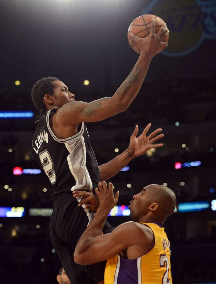 Kawhi Leonard (2) of the Spurs is called for a charge on Kobe Bryant (24) of the Los Angeles Lakers at Staples Center on Nov. 13, 2012 in Los Angeles.