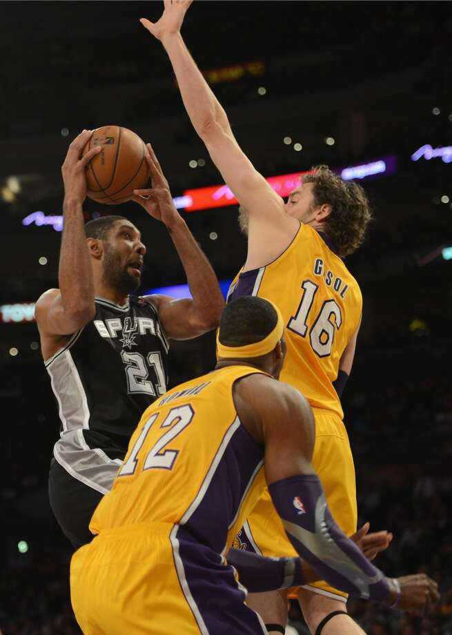 Tim Duncan (21) of the Spurs scores on a layup around Pau Gasol (16) and Dwight Howard (12) of the Los Angeles Lakers at Staples Center on Nov. 13, 2012 in Los Angeles.