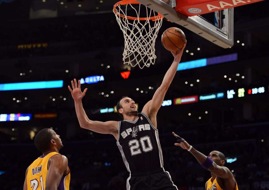 Manu Ginobili (20) of the Spurs scores on a layup between Chris Duhon (21) and Antawn Jamison (4) of the Los Angeles Lakers at Staples Center on Nov. 13, 2012 in Los Angeles.