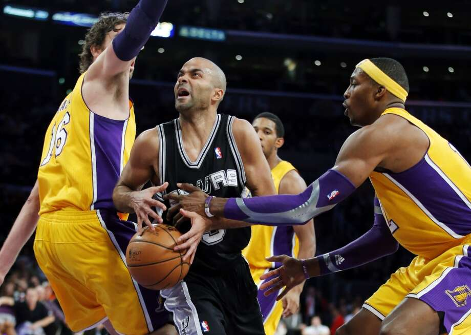 The Spurs\' Tony Parker (center) is defended by Los Angeles Lakers\' Dwight Howard (right) and Pau Gasol in the first half in Los Angeles, Tuesday, Nov. 13, 2012.