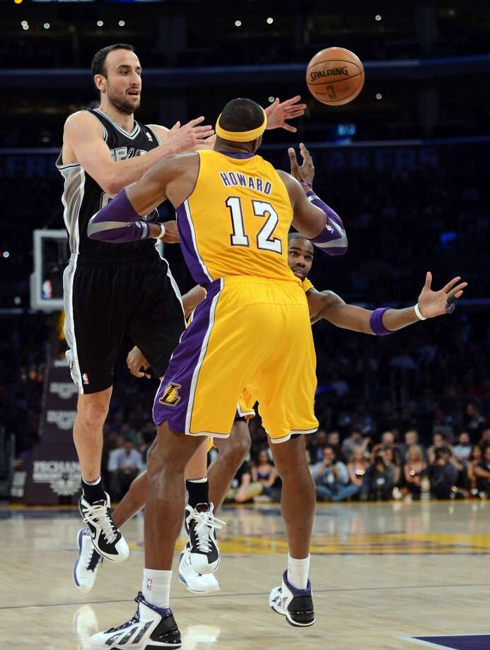 Manu Ginobili (20) of the Spurs makes a pass in front of Dwight Howard (12) and Antawn Jamison (4) of the Los Angeles Lakers during a 84-82 Spurs win at Staples Center on Nov. 13, 2012 in Los Angeles.