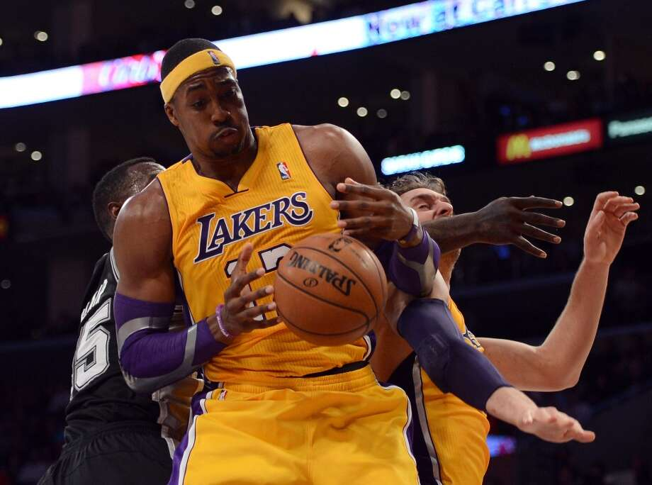 Dwight Howard (12) of the Los Angeles Lakers grabs a rebound from teammate Pau Gasol (16) against the Spurs at Staples Center on Nov. 13, 2012 in Los Angeles.