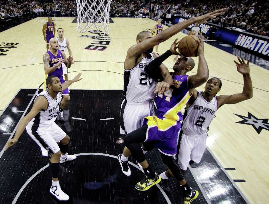 Los Angeles Lakers\' Kobe Bryant (24) is blocked by San Antonio Spurs\' Tim Duncan (21) and Kawhi Leonard (2) as he drives to the basket during the first quarter of an NBA basketball game on Wednesday, Jan. 9, 2013, in San Antonio. Photo: Eric Gay, Associated Press / AP