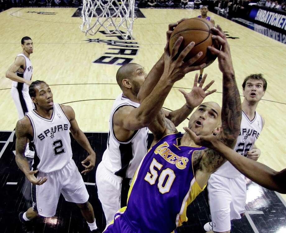 Los Angeles Lakers\' Robert Sacre (50) is blocked by San Antonio Spurs\' Tim Duncan, center, while trying to score during the first quarter of an NBA basketball game on Wednesday, Jan. 9, 2013, in San Antonio. Photo: Eric Gay, Associated Press / AP