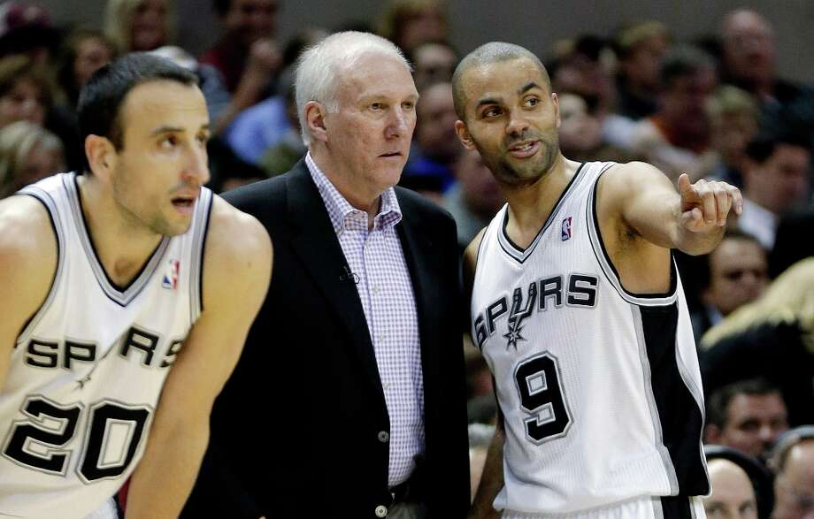 San Antonio Spurs head coach Gregg Popovich, center, talks with Tony Parker (9), of France, during the first quarter of an NBA basketball game against the Los Angeles Lakers, Wednesday, Jan. 9, 2013, in San Antonio. Spurs\' Manu Ginobili (20), of Argentina, looks on. Photo: Eric Gay, Associated Press / AP