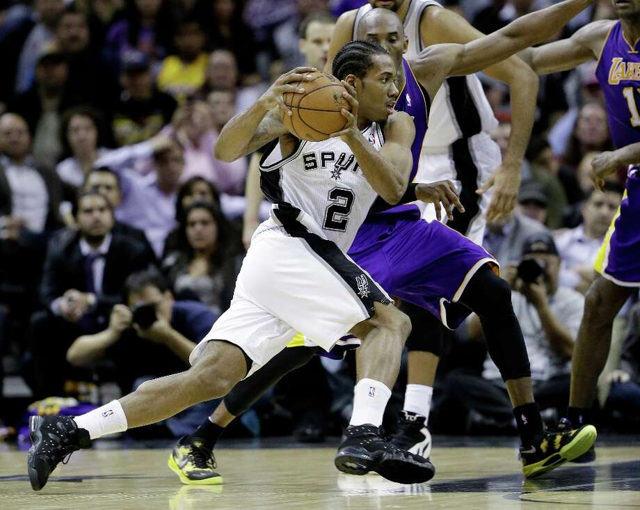 San Antonio Spurs\' Kawhi Leonard (2) reaces around Los Angeles Lakers\' Kobe Bryant, right, during the fourth quarter of an NBA basketball game on Wednesday, Jan. 9, 2013, in San Antonio. San Antonio won 108-105. Photo: Eric Gay, Associated Press / AP