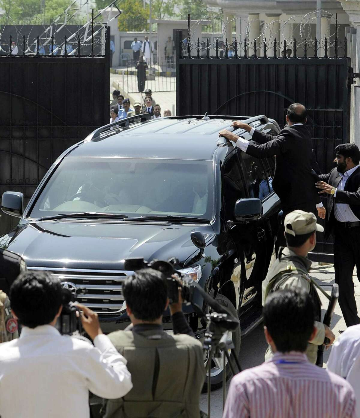 """Security forces escort a vehicle carrying former Pakistani President Pervez Musharraf as he flees from court in Islamabad after his bail was revoked. The judge ordered the city's police chief to appear before the court to explain why Musharraf was not arrested and to ensure action is taken against policemen """"who remained napping"""" instead of performing their duties."""