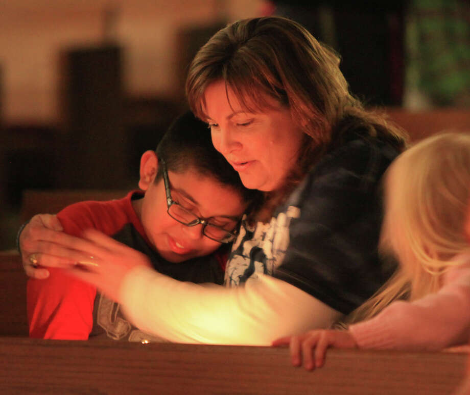 Karen Bernsen hugs Eric Garcia, 12, as her daughter Katy Bernsen, 5, looks on,Thursday April 18, 2013, during a candlelight vigil at Church of the Assumption in West, Tx. for the explosion at a fertilizer plant that occurred Wednesday evening. Photo: Edward A. Ornelas, San Antonio Express-News / © 2013 San Antonio Express-News