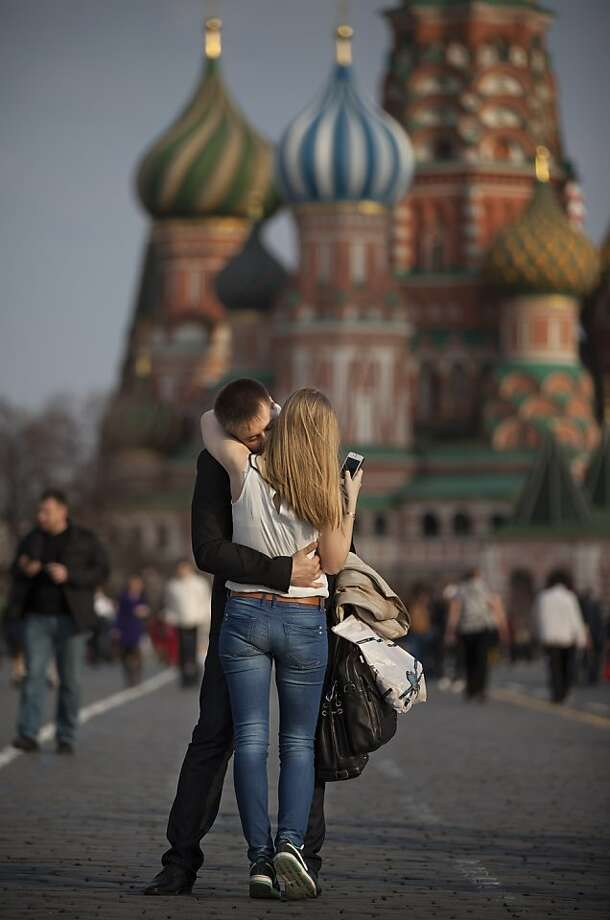 She says she loves him, but whom is she texting? A couple embrace on warm evening in Moscow's Red Square. Photo: Alexander Zemlianichenko, Associated Press