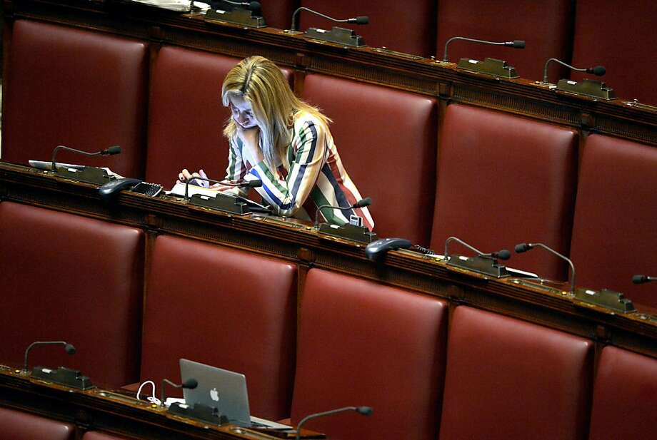 An unidentified deputy follows the vote count on a tablet on April 18, 2013 at the Italian parliament in Rome following a second round of voting to elect a new president after a first round failed to secure a victor in a ballot many hope will herald the end of a two-month impasse over a new government but which threatens fresh political divisions. In a last-minute agreement on April 17, Italy's two main political blocs had agreed to back Franco Marini, a pipe-smoking 80-year-old seen as having formidable political skills.  AFP PHOTO / ANDREAS SOLAROANDREAS SOLARO/AFP/Getty Images Photo: Andreas Solaro, AFP/Getty Images