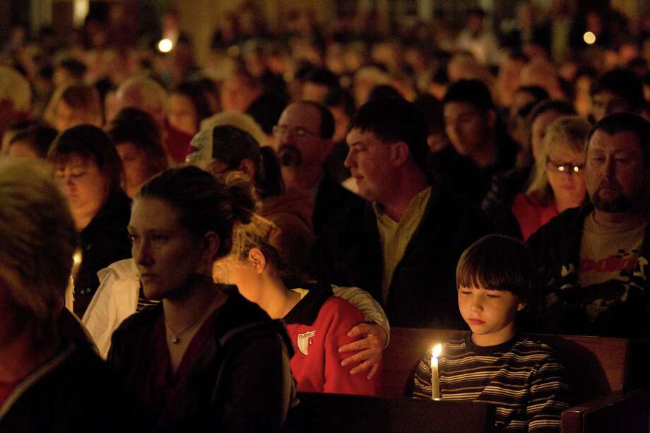 Clayton Tribble, 9, of West sits during a candle light vigil held at St. Mary's of Assumption Catholic Church as more than 500 gathered to mourn those hurt and killed in the West Fertilizer Co. plant explosion Thursday, April 18, 2013, in West, Texas. Photo: Johnny Hanson, Houston Chronicle / © 2013  Houston Chronicle