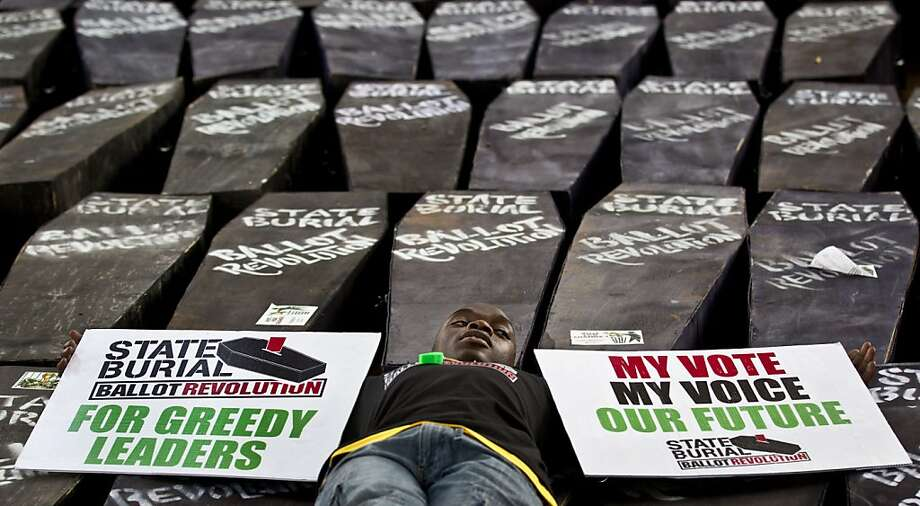 "FILE - In this Wednesday, Jan. 16, 2013 file photo, a demonstrator lies on mock coffins on which are written ""State Burial, Ballot Revolution"", before the coffins were carried to the Parliament and set on fire to protest against an attempt by Members of Parliament (MPs) to award themselves a $110,000 bonus, which was later vetoed by the president, in Nairobi, Kenya. Even before they begin their latest session in earnest, newly elected Kenyan parliamentarians are demanding a pay increase after the lavish wages legislators in the previous term earned were reduced, and one legislator even petitioned parliament on Thursday, April 18, 2013 to impeach members of the government commission that reduced their salaries. (AP Photo/Ben Curtis, File) Photo: Ben Curtis, Associated Press"