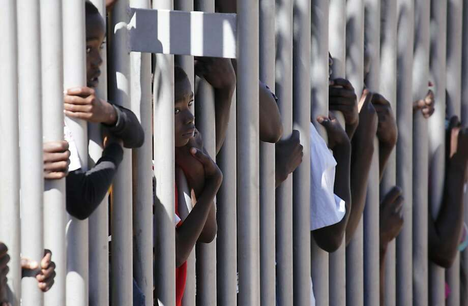 Youths peek through a barrier as they wait to enter a stadium where Zimbabwe's 33rd independence celebrations are being held, Harare, Thursday, April, 18, 2013. (AP Photo/Tsvangirayi Mukwazhi) Photo: Tsvangirayi Mukwazhi, Associated Press