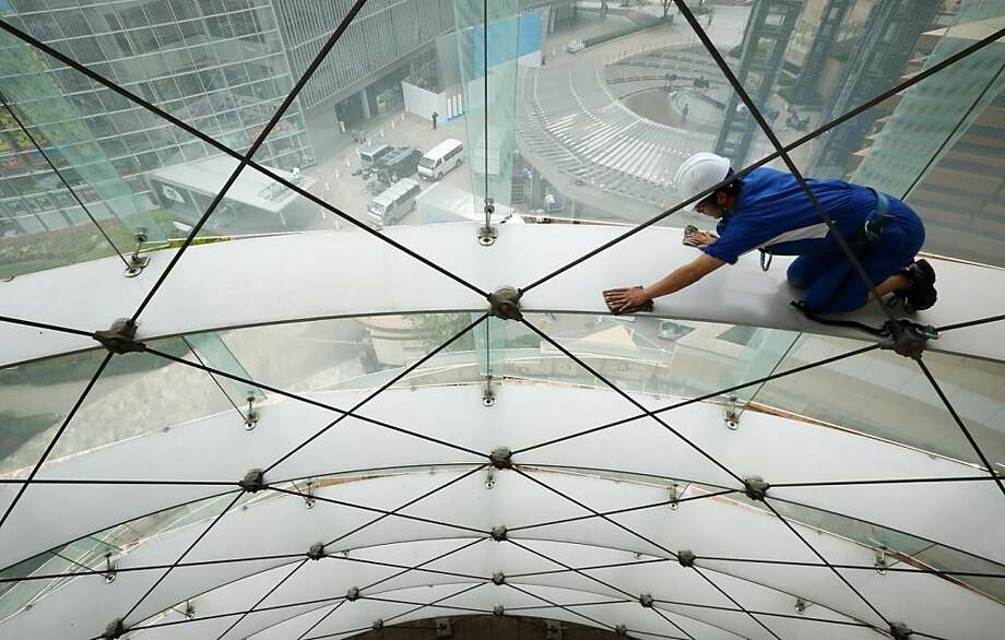 Bloomberg Photo Service 'Best of the Week': A worker cleans the windows inside the Roppongi Hills Mori Tower, operated by Mori Building Co., in Tokyo, Japan, on Wednesday, April 17, 2013. While financial firms have cut staff in Japan, technology companies have boosted hiring, and as bankers vacated offices at Roppongi Hills, companies including Google Inc. and Lenovo Group Ltd. moved in. As early as this month, Apple Inc. will also make the complex its home in Japan, two people familiar with the plan said in January. Photographer: Tomohiro Ohsumi/Bloomberg Photo: Tomohiro Ohsumi, Bloomberg