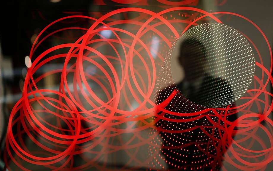 A visitor watches the mirror 'Circles (Curved Down Under)' by German artist Hans Kotter at the ART COLOGNE fair in Cologne, Germany, Thursday, April 18, 2013. International  art dealers  and artists show modern and contemporary art  from April 19  till April 22, 2013 at the fairground in Cologne. (AP Photo/Frank Augstein) Photo: Frank Augstein, Associated Press