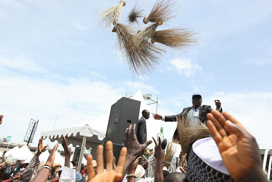 A man throws palm-frond brooms, a symbol of the new All Progressive Congress party, at a rally in Lagos, Nigeria, on Thursday, April 18, 2013. Three opposition political parties in Nigeria are creating a single, unified front to challenge the oil-rich nation's leaders ahead of the next presidential election. Together, the new All Progressive Congress party could pose the first serious political challenge to the ruling People's Democratic Party, which has controlled Nigeria since it became a democracy in 1999. (AP Photo/Jon Gambrell) Photo: Jon Gambrell, Associated Press
