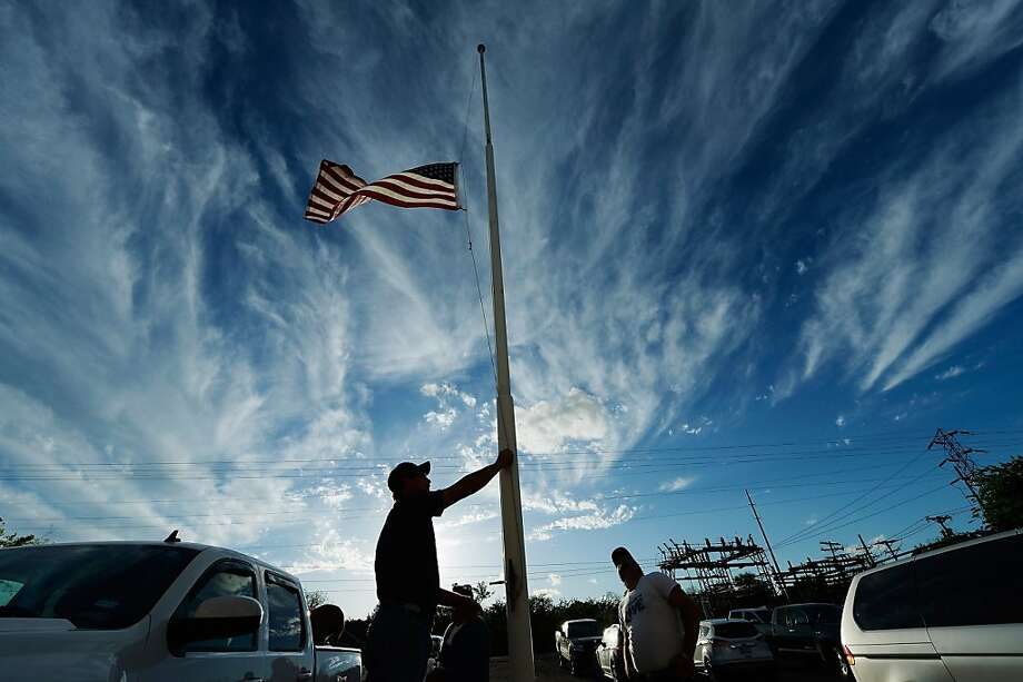 WEST, TX - APRIL 18:  Bill Warren, a member of Veterans of Foreign Wars Post 4819, lowers the U.S. flag to half staff in memory of victims of the West Fertilizer Company explosion April 18, 2013 about 20 miles north of Waco in West, Texas. A fiery explosion that damaged or destroyed buildings within a half-mile radius ripped through the facility last night, injuring more than 160 people and killing an unknown number of others.  (Photo by Kevork Djansezian/Getty Images) Photo: Kevork Djansezian, Getty Images
