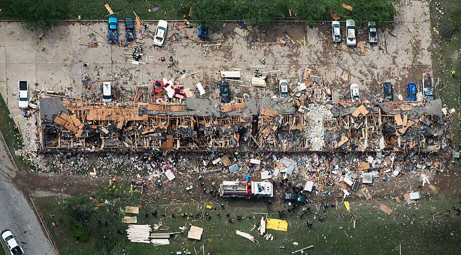 In this aerial photo, law enforcement and rescue personnel search the damage to an apartment complex from the explosion of the West Fertilizer plant on Thursday, April 18, 2013, in West, Texas. A massive explosion at the plant killed as many as 15 people and injured more than 160, officials said overnight. (AP Photo/Houston Chronicle, Smiley N. Pool) Photo: Smiley N. Pool, Associated Press
