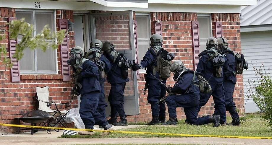 Armed federal agents wearing what appeared to be hazardous material suits and breathing apparatus entered the West Hills Subdivision home of Paul Kevin Curtis in Corinth, Miss., Thursday evening April 18, 2013. Law enforcement officials blocked off the dwelling after taking Curtis into custody under the suspicion of sending letters covered in ricin to the U.S. President Barack Obama and U.S. Sen. Roger Wicker, R-Miss. (AP Photo/Rogelio V. Solis) Photo: Rogelio V. Solis, Associated Press