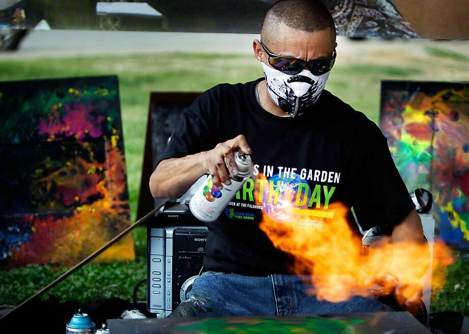 Spray paint artist Martin Martinez from Dallas, dries a coat of paint the fast way while giving a demonstration of his craft during the University of Memphis Earth Day Event at U of M's Urban Garden Thursday April 18, 2013 in Memphis, Tenn. In addition to food, educational demonstrations, and music, U of M students released some 150 butterflies in the garden to honor the upcoming holiday.  (AP Photo/The Commercial Appeal, Jim Weber) Photo: Jim Weber, Associated Press