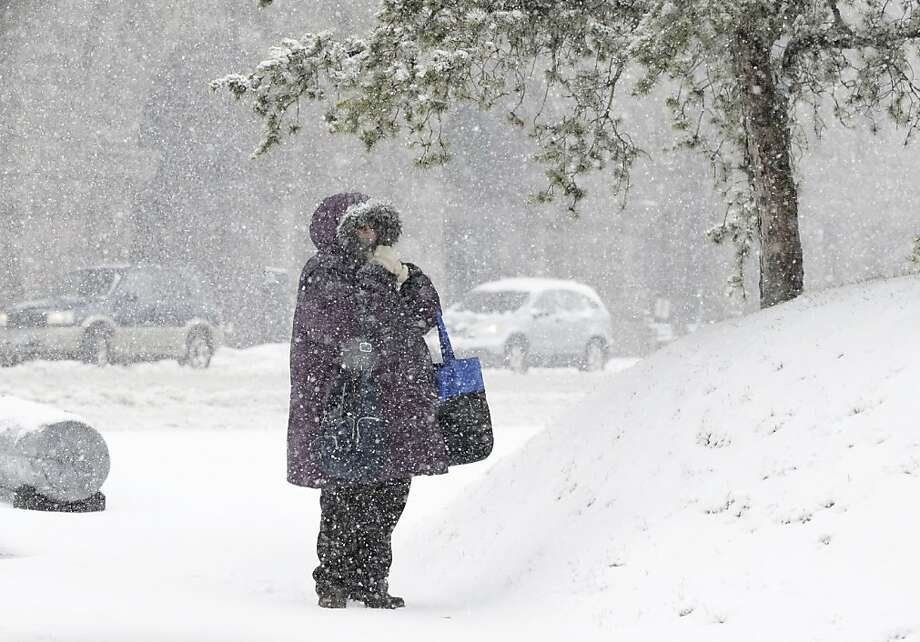 A woman braves blowing snow while she waits at a bus stop as a Spring storm hit Minneapolis and other parts of the state Thursday, April 18, 2013. (AP Photo/Jim Mone) Photo: Jim Mone, Associated Press