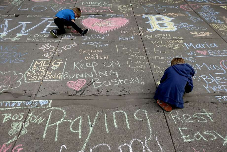 Two young boys leave messages with chalk on a sidewalk near the finish line of Monday's Boston Marathon explosions, which killed at least three and injured more than 140, Thursday, April 18, 2013, in Boston. (AP Photo/Matt Rourke) Photo: Matt Rourke, Associated Press