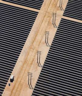 "Bloomberg Photo Service 'Best of the Week': Solar panels are seen in this aerial photograph of First Solar Inc.'s Desert Sunlight Solar Farm in Mojave Desert, California, U.S., on Friday, April 5, 2013. First Solar Inc., the largest thin-film panel manufacturer, sees ""significant growth"" in renewable energy projects being developed in the Middle East and North Africa by the end of 2014. Photographer: Tim Rue/Bloomberg"